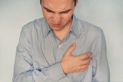 Equipaggi avere mano della tenuta di dolore del cuore sul suo concetto di sanità di attacco di cuore o del colpo del petto immagine stock