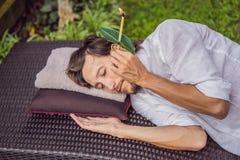 Equipaggi avere una terapia della candela dell'orecchio contro il contesto di un giardino tropicale fotografie stock libere da diritti