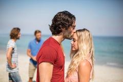 Equipaggi baciare l'amica sulla fronte contro gli amici alla spiaggia Fotografia Stock