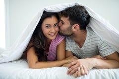 Equipaggi baciare la donna sotto la coperta nella camera da letto Fotografia Stock Libera da Diritti