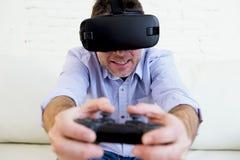 Equipaggi a casa lo strato del sofà del salone eccitato facendo uso del gioco degli occhiali di protezione 3d Immagini Stock