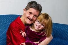 Equipaggi con gli abbracci di sindrome dei bassi la sua pronipote entrambe che sorridono fotografia stock libera da diritti