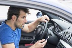 Equipaggi condurre l'automobile e la tenuta del telefono, conce pericoloso immagini stock libere da diritti