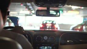 Equipaggi condurre l'automobile sciccosa nel parcheggio sotterraneo, l'autista dell'albergo di lusso, occupazione archivi video