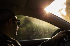 Equipaggi condurre un'automobile alla luce di cielo di sera del tramonto Sunglasse d'uso Fotografie Stock