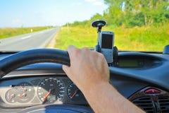 Equipaggi condurre un'automobile con il telefono su un parabrezza Immagine Stock