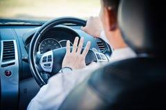 Equipaggi condurre un'automobile con la mano sul bottone di corno Immagini Stock