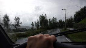 Equipaggi condurre un'automobile sulla strada pubblica durante la piovosità pesante con le goccioline di acqua sui tergicristalli fotografia stock