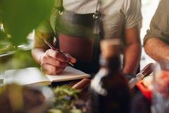 Equipaggi creare la nuova ricetta del cocktail e la presa delle note Fotografia Stock Libera da Diritti