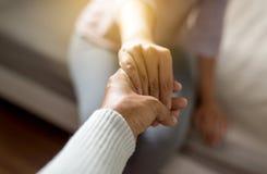 Equipaggi dare la mano alla donna depressa, psichiatra che si tiene per mano il paziente, concetto di sanità di Meantal fotografia stock