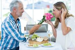 Equipaggi dare le rose rosa alla moglie in ristorante Fotografia Stock Libera da Diritti