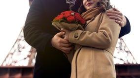 Equipaggi delicatamente abbracciare la donna cara con i fiori piacevoli in mani, romanzesche a Parigi Immagini Stock Libere da Diritti
