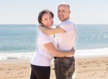Equipaggi e una donna di mezza età che si siede sulla spiaggia fotografie stock