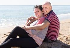 Equipaggi e una donna di mezza età che si siede sulla spiaggia fotografia stock libera da diritti