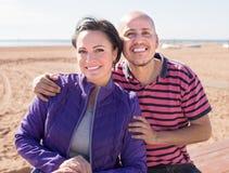 Equipaggi e una donna di mezza età che si siede sulla spiaggia immagini stock libere da diritti