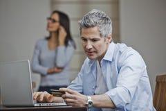 Equipaggi fare l'acquisto online con la sua moglie che parla su un fon mobile immagine stock
