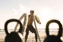 Equipaggi fare l'addestramento di forma fisica alla spiaggia con le corde di battaglia ed il KE Fotografia Stock