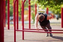 Equipaggi fare l'addestramento fisico sulle barre trasversali su un fondo del parco Concetto professionale di allenamento Copi lo Fotografie Stock