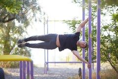 Equipaggi fare l'addestramento fisico sulle barre trasversali su un fondo del parco Concetto professionale di allenamento Copi lo Fotografia Stock Libera da Diritti