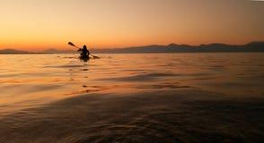 equipaggi fare la canoa al tramonto in oceano immagini stock