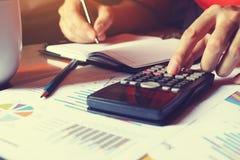 Equipaggi fare la finanza e calcoli sullo scrittorio circa costo a casa offic immagine stock