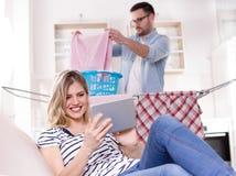 Equipaggi fare la lavanderia mentre donna che riposa sul sofà fotografia stock