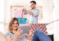 Equipaggi fare la lavanderia mentre donna che riposa sul sofà fotografia stock libera da diritti