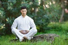 Equipaggi fare la meditazione che si siede sulla pietra all'aperto Immagini Stock