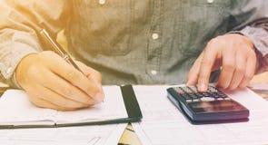 Equipaggi fare le finanze con per mezzo del calcolatore e la scrittura della nota nel hom Fotografia Stock