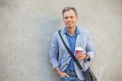 Equipaggi fare una pausa la parete con una tazza in sue mani Immagine Stock Libera da Diritti