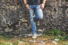 Equipaggi fare una pausa la vecchia parete, i jeans strappati blu d'uso e le scarpe da tennis della tela Fotografie Stock Libere da Diritti