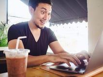 Equipaggi felice ed ecciti con il suo successo nel computer portatile fotografia stock