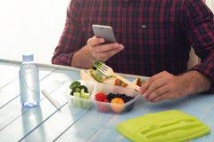 Equipaggi fotografare la scatola di pranzo con alimento sano che si siede alla tavola Immagini Stock