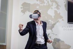 Equipaggi gli occhiali di protezione d'uso di realtà virtuale, uomo d'affari che fa i gesti Immagini Stock Libere da Diritti