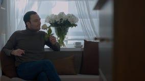 Equipaggi gli odori una rosa e sognare della sua moglie nel salone fotografia stock libera da diritti