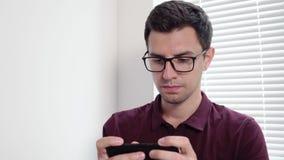 Equipaggi gli sms che mandano un sms facendo uso del app sullo Smart Phone nell'ufficio che fa una pausa la finestra Giovane usan archivi video