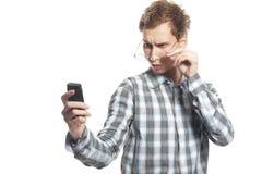 Equipaggi gli sms della lettura sul suo telefono sopra bianco Immagini Stock