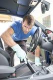 Equipaggi hoovering la cabina dell'automobile, pulente il concetto fotografie stock
