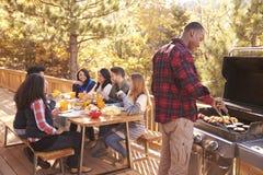 Equipaggi i barbecue per gli amici ad una tavola, su una piattaforma in una foresta Immagini Stock
