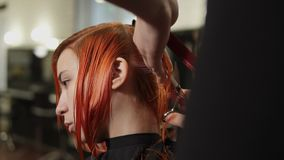 Equipaggi i capelli del ` s della donna di taglio del parrucchiere nel salone di bellezza La giovane donna le che ottiene i capel archivi video