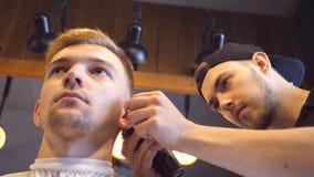 Equipaggi i capelli di taglio del barbiere del cliente maschio con il tagliatore al negozio di barbiere Processo di Hairstyling A video d archivio