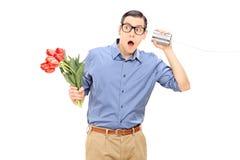 Equipaggi i fiori della tenuta e l'ascolto tramite il telefono del barattolo di latta Fotografie Stock Libere da Diritti