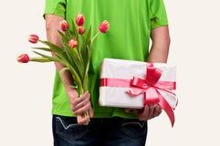 Equipaggi i fiori ed il contenitore di regalo nascondentesi dietro il suo indietro Immagine Stock