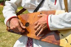 Equipaggi i giochi uno strumento musicale russo tradizionale antico - gusli Fotografia Stock