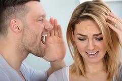 Equipaggi i grida in suo orecchio del ` s della moglie Fotografia Stock Libera da Diritti