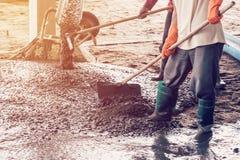 Equipaggi i lavoratori che spargono la miscela di calcestruzzo di recente versata su costruzione Fotografie Stock Libere da Diritti
