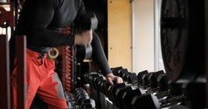 Equipaggi i muscoli del bicipite di addestramento del braccio con le teste di legno in video del primo piano della palestra 4k Cu video d archivio