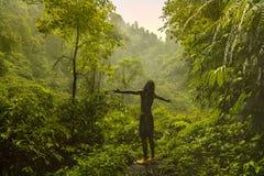 Equipaggi i soggiorni con il suo indietro davanti alla giungla e sollevi le sue mani ai lati Concetto di libertà Fotografia Stock Libera da Diritti