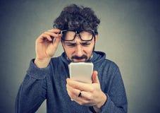 Equipaggi i vetri d'uso che hanno difficoltà che vede il messaggio di telefono cellulare fotografie stock