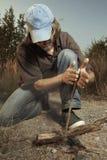 Equipaggi il campeggio in natura che fa il fuoco con attrito di bastone di legno a mano immagini stock libere da diritti
